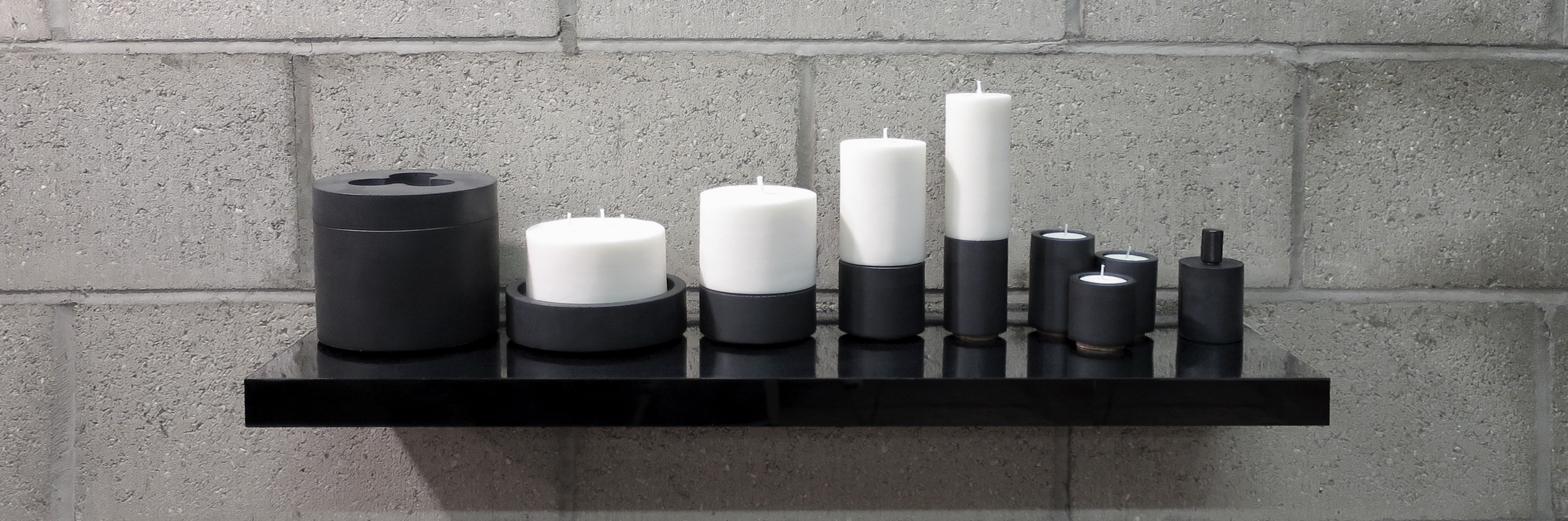 A collection of modular and stackable concrete holders and natural wax pillar candles